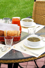 Restaurant table with soup and jug of juice