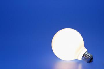 A lit up light bulb on a blue background.