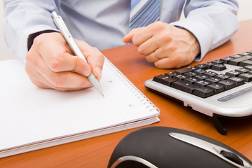 Business man writing in a notebook.