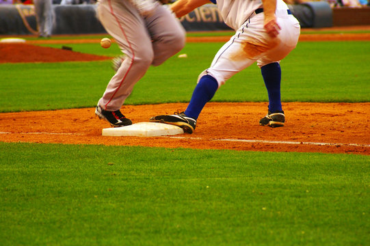 baeball player running to first base ahead of the throw