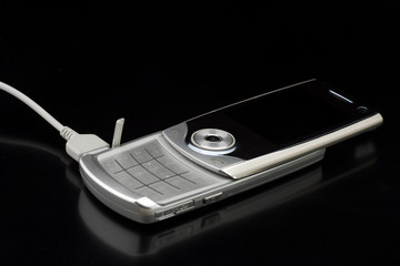 Silver cell phone conected to charger - on shiny black