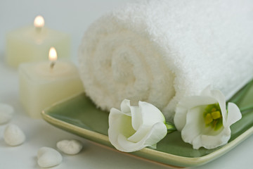 Spa setting with Beautiful white flowers, towel and candle