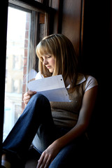Teenage girl sitting on a window and reading school notes.