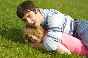 Young happy couple laying on a green grass