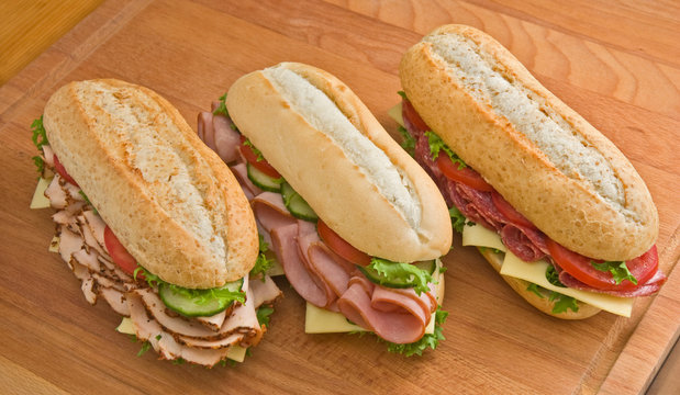 Turkey, ham and salami sandwiches on a wooden surface