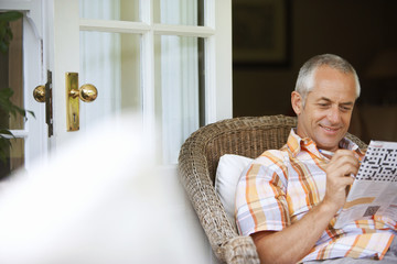 Mature man relaxing in wicker chair at home, doing newspaper crossword, smiling, focus on background