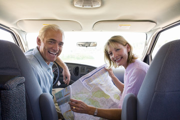 Mature couple with  map in motor home, smiling, portrait