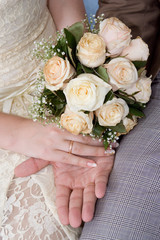 Hands of a newly-married couple with a bouquet, close up