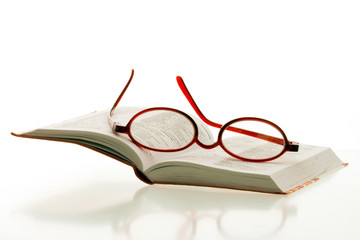 red reading glasses on the pages of an open book