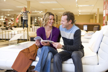 Young couple with brochure in furniture shop, smiling at each other