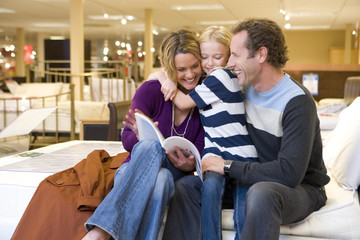 Family of three in furniture shop, daughter (6-8) embracing mother