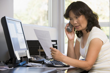 Woman in home office with paperwork using telephone