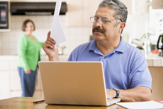 Man in kitchen with laptop and paperwork