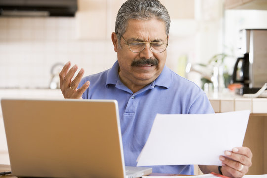 Man in kitchen with laptop and paperwork frustrated