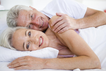 Couple lying in bed together smiling