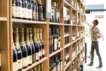 Woman looking at wine in shop