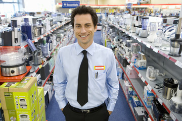 Young salesman in electronics aisle, hands in pockets, smiling, porttrait
