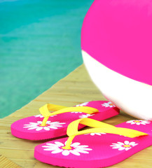 Beach ball and sandals on dock