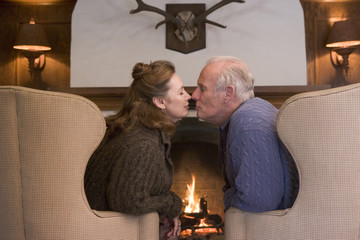Couple sitting in living room by fireplace kissing