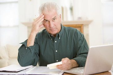 Man with laptop and paperwork looking frustrated