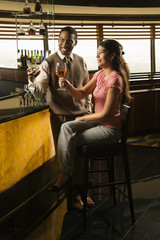 Couple toasting at bar.