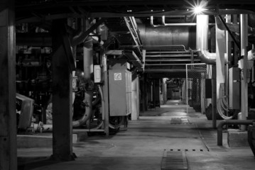 Machinery, pipes, and boilers at factory black and white