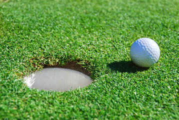 Golf Ball Next to Cup with Shallow Depth of Field
