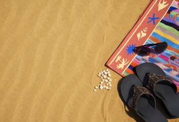 Beach towel and shoes on the sand