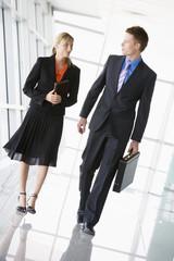 Two businesspeople walking in corridor talking