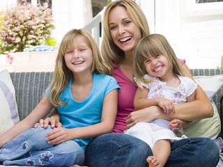 Woman and two young girls sitting on patio smiling