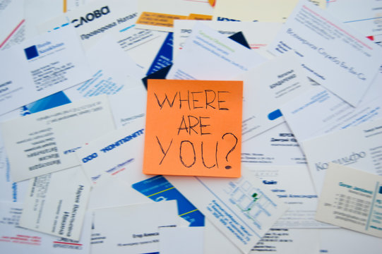 """A note """"where are you?"""" over business cards in disorder"""
