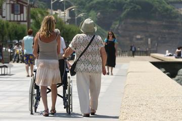 femmes qui marchent en poussant un fauteuil roulant