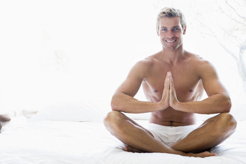 Man sitting on bed meditating and smiling