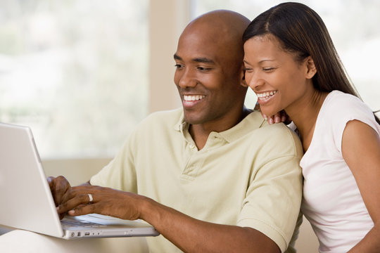 Couple in living room using laptop and smiling