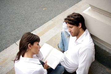 Studenten Paar vor der Uni beim Lesen