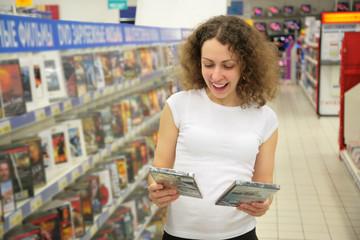 Spoed Foto op Canvas Muziekwinkel young woman in shop chooses disk