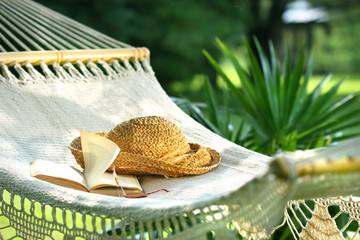 Hammock, book, hat, and glasses on a sunny day