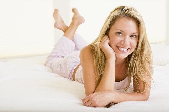 Woman lying in bedroom smiling