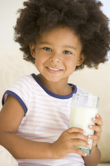 Young girl indoors drinking milk smiling