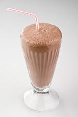 chocolate milkshake in a glass with  straw.