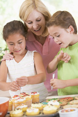Woman with two children decorating cookies smiling