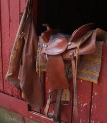 saddle and chaps on barn door