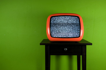 Red old retro television on green room