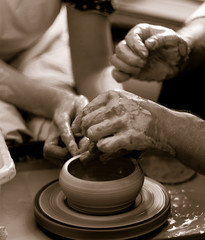 teaching to shape a earthenware on a potter's wheel