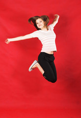 attractive girl jumping of joy over red