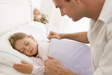 Man waking young girl in bed smiling