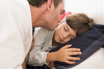 Man waking young boy in bed with kiss