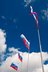 Four waving Russian flags with St.Petersburg symbol on top
