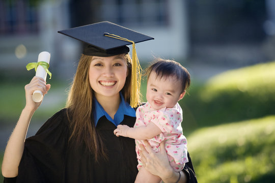 Young woman graduate holding baby