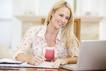 Woman in dining room with laptop smiling
